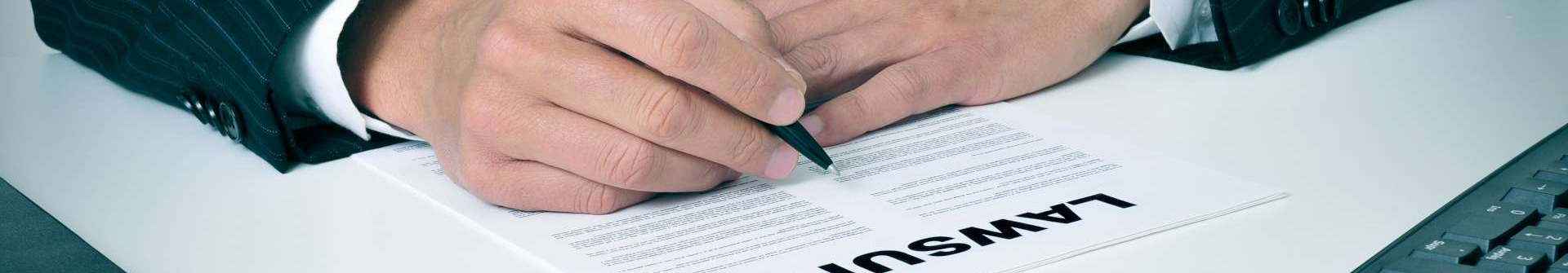 a man signing a lawsuit document.